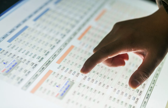 hand pointing at data report on screen